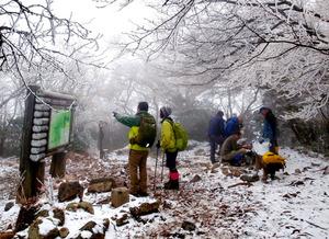 樹氷に覆われた万三郎岳の山頂。左の登山者の手前、案内板の前に1等三角点が見える