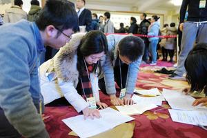 全人代の開幕日、速報するため床に配布資料を広げて読み込む記者たち=5日午前8時、中国・北京、矢木隆晴撮影