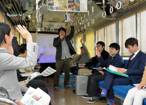 電車内でのプレゼンを聞く参加者ら=福井市