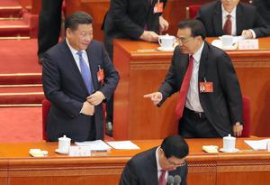 全人代の開幕日、人民大会堂から退席する際に言葉を交わす習近平国家主席(左)と李克強首相=5日午前10時43分、中国・北京、矢木隆晴撮影