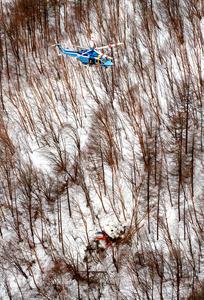 墜落した防災ヘリと救助活動を行う県警のヘリ=5日午後5時5分、鉢伏山付近、朝日新聞社ヘリから、竹花徹朗撮影