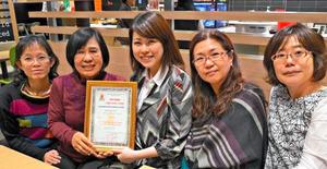ベトナムのダナン枯れ葉剤被害者の会(DAVA)からの感謝状を手にするアレン・ネルソン奨学会沖縄の宜野座映子代表(左から2人目)ら