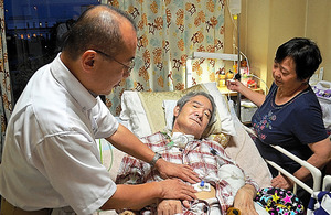 患者の胃ろうチューブを交換する医師(左)と様子を見守る妻=マンスリーコラム「老いの現場を歩く」〈胃ろうにする?しない? 「心のふたがとれた」とき〉から