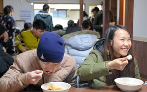 今年1月に完成した食堂で、朝食の中国がゆを食べるベトナム人のグェン・ティ・レさん(右)。「今までで一番ベトナムの味に近いよ」=大阪市生野区