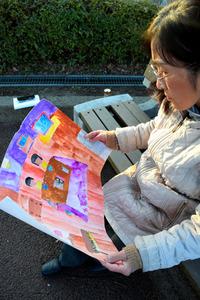福島県南相馬市にあった自宅の絵を見る柚原令子さん。小学生だった次女が描いた=仙台市若林区