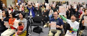 参加者たちは「#保育園に入りたい」と書かれた紙を一斉に掲げた=千代田区