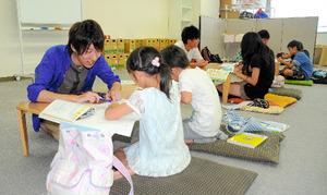 「フレール」のメンバーと子どもたちに勉強を教える近野秀亮さん(左)=2014年7月、山形市