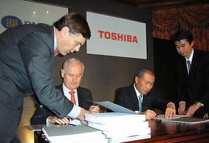 ウェスチングハウスの買収契約にサインする東芝の西田厚聡社長(当時、右から2人目)=2006年2月、ロンドン