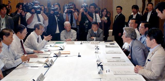 経済財政諮問会議で小泉首相(着席右から2人目)らと向き合う牛尾治朗さん(同左から3人目)。右端は竹中経済財政担当相=2005年9月27日、首相官邸
