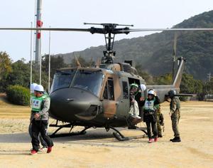 孤立集落の救援訓練で自衛隊のヘリから降りる住民ら=佐伯市米水津