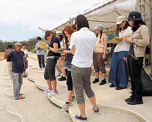 沖縄・辺野古の海辺で話を聞く学生たち=山田教授提供