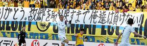 東日本大震災直後から使われている横断幕の前でプレーする仙台と神戸の選手たち