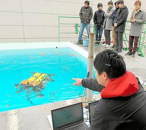 実験用のプールで、土器などの観察のために開発された水中ロボットを動かす学生ら=滋賀県草津市の立命館大学