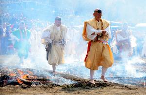 煙が立ち込める中、火の上を渡る修験者ら=八王子市高尾町