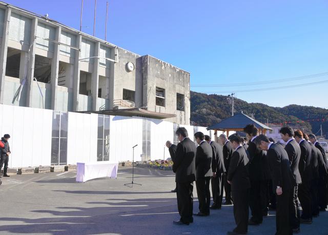 保存か解体かの議論が続いている旧役場庁舎前で祈りを捧げる役場職員=大槌町新町