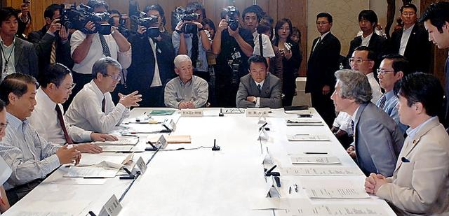 経済財政諮問会議で小泉首相(着席右から2人目)らと向き合う牛尾治朗さん(同左から3人目)=2005年9月27日、首相官邸