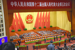 全体会議が開かれる人民大会堂。記者席から肉眼では、舞台上の習近平国家主席や李克強首相の表情まではうかがえない=8日、中国・北京、延与光貞撮影