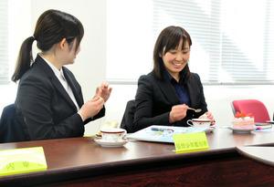 用意されたケーキやコーヒーを手にして、打ち解けた雰囲気で話をする女性内定者ら=福岡市