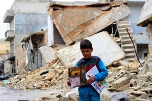シリアのアレッポ東部で1月、ユニセフのボランティアが配った資料を手にする子ども。ユニセフ提供=AP