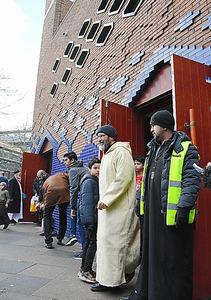 礼拝に訪れた人でにぎわうブラウエモスク。出入り口の上には小型の監視カメラがあり、警備員も見守る=アムステルダム、吉田美智子撮影