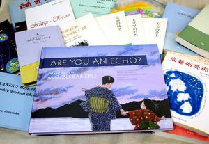 米国で出版された「ARE YOU AN ECHO?(こだまでしょうか)」(手前)と、中国や韓国などで出されている金子みすゞの詩集