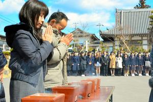 神戸市の中学校OBら(奥)の合唱を聴きながら、焼香をして犠牲者を悼む七回忌法要の参列者=宮城県気仙沼市波路上牧の地福寺