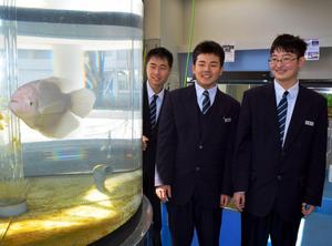 西川宗一郎部長(右)ら多度津高校生物科学部の部員たち。左の水槽で泳ぐのはオスフロネームスグラミー=多度津町栄町1丁目