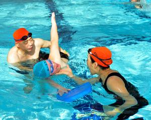ボランティアに指導を受けながら息継ぎの練習をする参加者=八戸市河原木