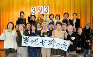 集めた署名の数「393」を掲げる「築地女将さん会」のメンバー=東京都中央区築地