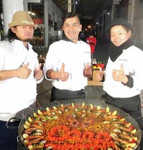 日高勇さん(中央)らが作った「広島カープ」をイメージしたパエリア。イセエビなど地元食材をふんだんに使った=1月1日、日南市の油津商店街