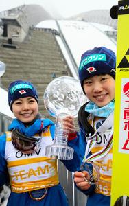 今シーズンの個人総合優勝トロフィーを手に笑顔の高梨沙羅と2位の伊藤有希(右)=オスロ、林敏行撮影