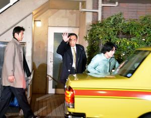 報道陣に右手を上げ、タクシーに乗り込む籠池泰典理事長(中央)と家族=東京都内