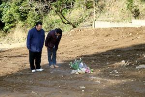新所地区の山内博史区長(左)と江藤俊雄副区長が亡くなった片島信夫さん、利栄子さん夫妻の慰霊に訪れた。辺りは解体が進み、更地となっていた=16日午前9時1分、熊本県南阿蘇村立野、金子淳撮影