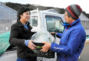 関谷裕幸さん(右)から野菜を受け取る馬場大治さん=白河市白坂地区