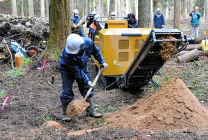 粉砕したほだ木をまく作業員。背後に保管されているほだ木が山積みになっている=登米市