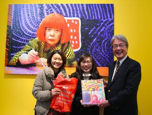 10万人目の入場者となった泉恵子さん(中央)と青木保・国立新美術館長(右)。左は友人=東京・六本木
