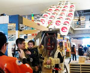 函館市で19日まで開かれている秋田県の観光PRイベント。竿燈(かんとう)が飾られて、なまはげも登場。来店した人たちは、写真を撮ったり、武家屋敷が有名な角館などの見どころを尋ねたりと、反応は上々だ=11日、函館蔦屋書店