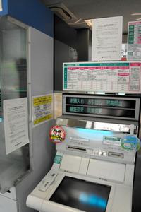 広島市内のATM。左側に、振り込みの一部制限を始めると説明する紙が貼られている