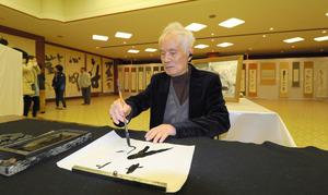 卒寿書展の会場で筆を運ぶ渕上清園さん=水俣市南福寺
