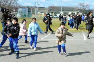 弾道ミサイル落下を想定した訓練で、校庭から屋内へ避難する児童ら=17日午前9時36分、男鹿市の北陽小学校、迫和義撮影