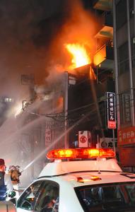 火の手が上がる建物に放水する消防隊員ら=18日午前1時すぎ、東京都千代田区