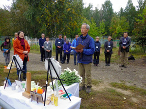 父の大野次郎さんの墓のあった一帯で、追悼の言葉を述べる信義さん=昨年9月2日、ロシアのイルクーツク州、信義さん提供