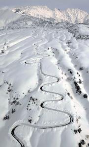 除雪作業が進む立山黒部アルペンルート。後方は立山=18日午後、富山県立山町、朝日新聞社ヘリから、筋野健太撮影