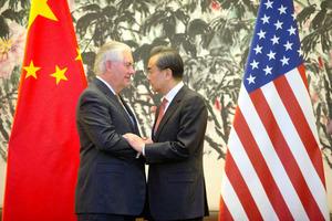 北京で18日、共同会見の後に握手をするティラーソン米国務長官(左)と中国の王毅外相=AFP時事
