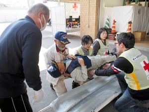 被災者をかかえ組み立てた担架で受ける参加者=大分市の日赤県支部