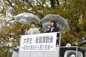 雨の中、若者の選挙権について演説した永友歩里さん(右)=宮崎市橘通東4丁目