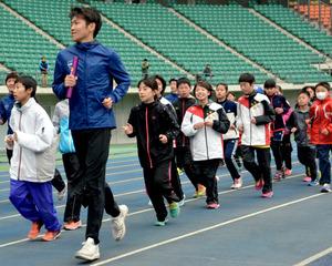 現役の選手とジョギングする子どもたち=大分市横尾