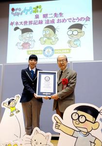公式認定証を受け取る泉昭二さん(右)=20日、東京・築地の朝日新聞社