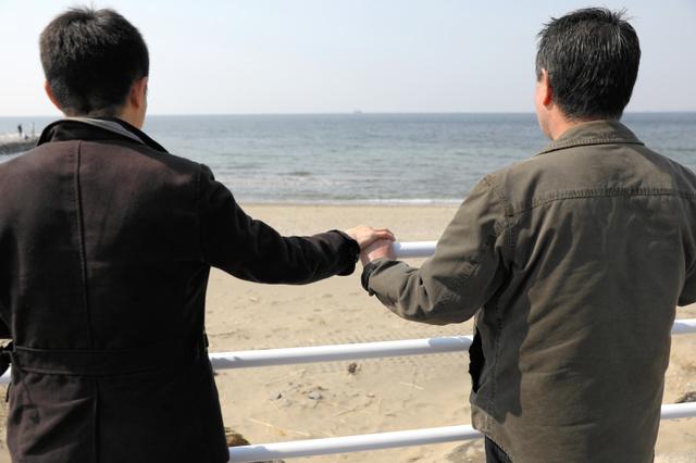 台湾籍の男性(左)と日本人のパートナーは手をつないで関東地方の海を見ていた=20日午前、林紗記撮影
