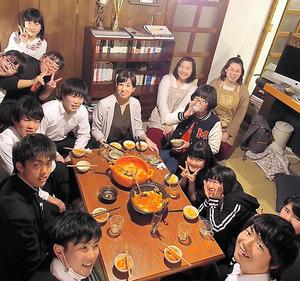 鍋を囲む子どもたちと、鴻巣麻里香さん(奥の右から4番目)らスタッフ=福島県白河市